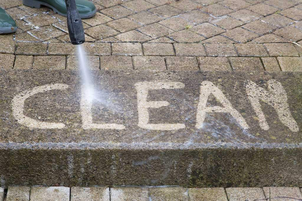 Power washing the word clean on the cement