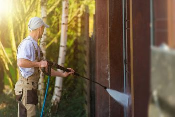 service technician performs power washing on a residential home
