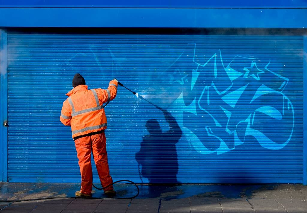 a man removes graffiti from commercial storefront