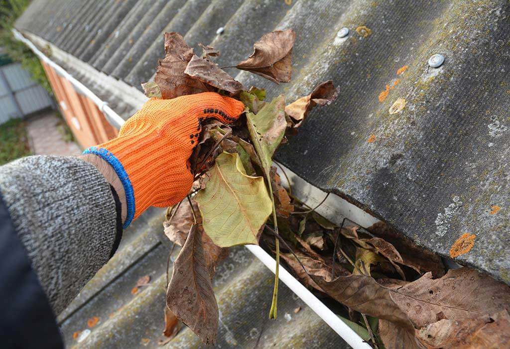A man with orange gloves gutter cleaning