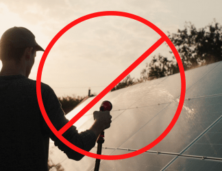 a man using hose water on solar panels