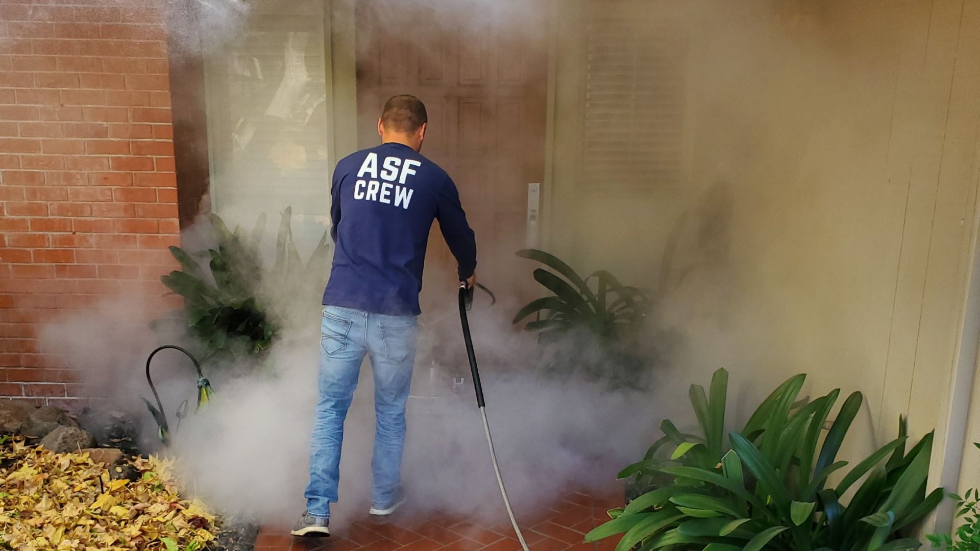 man cleans with a chemical free hot pressure washer