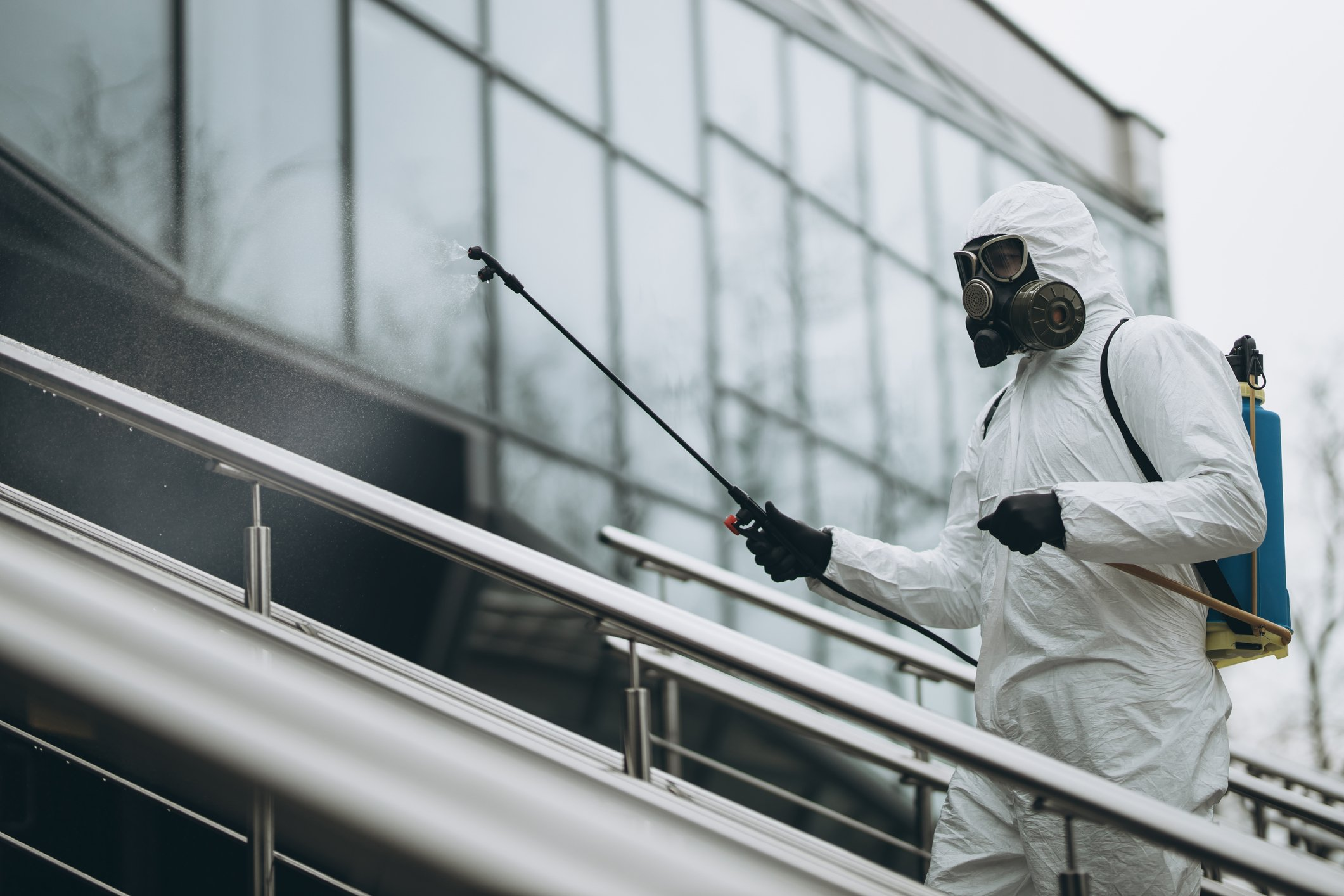 a man in a body suit disinfecting and sanitizing a commercial business